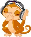 逗人喜爱的小的猴子听的音乐 免版税库存图片