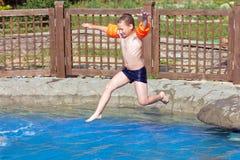 男孩在池跳 免版税库存图片