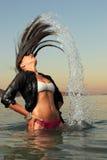 飞溅海水的女孩与她的头发 免版税库存图片