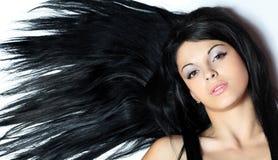 有平直的长的头发的年轻微笑的妇女 免版税图库摄影