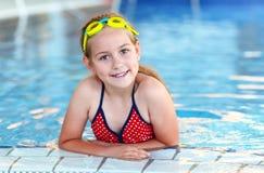 有风镜的愉快的女孩在游泳池 免版税库存图片