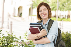 微笑的青少年的女学生外面与书 免版税库存照片