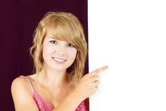 拿着空白符号的逗人喜爱的白肤金发的女孩 免版税图库摄影