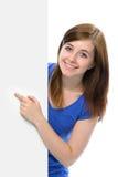 Το έφηβη δείχνει το δάχτυλό της σε ένα κενό χαρτόνι Στοκ φωτογραφία με δικαίωμα ελεύθερης χρήσης