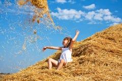 孩子投掷的干草 免版税库存图片