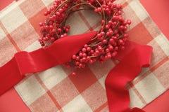 在格子花呢披肩的圣诞节浆果和丝带 免版税库存照片