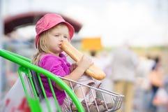 Το λατρευτό μωρό τρώει το μακρύ ψωμί, κάθεται στο κάρρο Στοκ εικόνα με δικαίωμα ελεύθερης χρήσης
