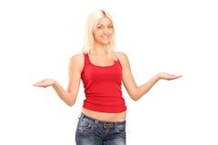 打手势与她的胳膊的美丽的少妇 免版税库存照片