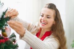 装饰圣诞树的微笑的少妇 免版税图库摄影