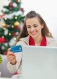 Ευτυχής γυναίκα που κάνει τα Χριστούγεννα ψωνίζοντας στο διαδίκτυο Στοκ εικόνες με δικαίωμα ελεύθερης χρήσης