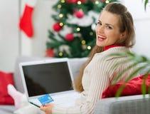 Γυναίκα που κάνει τα Χριστούγεννα ψωνίζοντας στο διαδίκτυο Στοκ Εικόνες