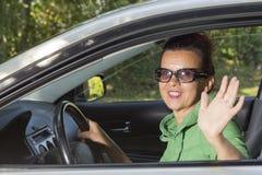 汽车挥动的你好的逗人喜爱的妇女 免版税图库摄影