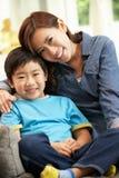 中国母亲和儿子坐沙发 免版税库存图片