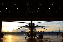 直升机剪影在飞机棚 免版税库存照片