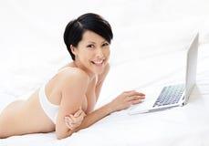 内衣的妇女在个人计算机工作 库存图片