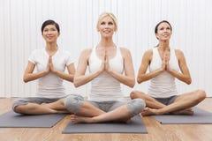 人种间组瑜伽位置的妇女 图库摄影