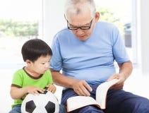 与孙子的祖父阅读书 免版税图库摄影