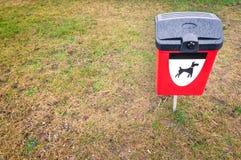 Κόκκινο δοχείο αποβλήτων σκυλιών στον πράσινο χορτοτάπητα στην περιοχή πάρκων. Στοκ φωτογραφία με δικαίωμα ελεύθερης χρήσης