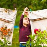 有晒衣夹和晒衣绳的五年女孩 免版税库存图片