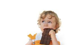 吃巧克力的逗人喜爱的子项 免版税库存照片