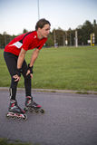 溜冰鞋的运动员从疲倦休息 免版税库存图片