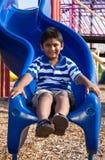 一个逗人喜爱的矮小的印第安男孩的纵向操场的 免版税库存图片