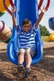 一个逗人喜爱的矮小的印第安男孩的纵向操场的 图库摄影
