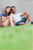 少年夫妇坐草 免版税库存照片