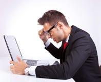 他的膝上型计算机的恼怒的商人 库存图片