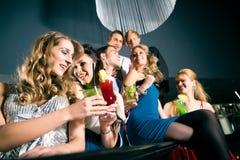 Люди в коктеилах клуба или штанги выпивая Стоковые Фото