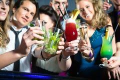 俱乐部或棒饮用的鸡尾酒的人们 免版税图库摄影