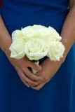 拿着白色玫瑰色婚礼花束的女傧相 免版税库存照片