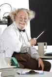 对黑板的微笑的异常科学家点 免版税库存图片