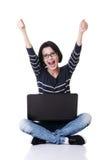 使用她的膝上型计算机,有拳头的愉快的少妇 免版税库存图片