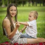 有男婴的母亲在公园 免版税库存图片