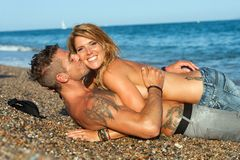 Сексуальные пары кладя на пляж камушка. Стоковые Фото