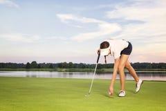 女孩拾起从杯子的高尔夫球运动员球。 免版税库存图片