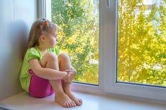 哀伤的女孩在视窗里 免版税库存图片