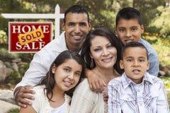 在被卖的房地产标志前面的西班牙家庭 免版税库存照片