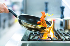 主厨在火炉的餐馆厨房里与平底锅 免版税库存图片