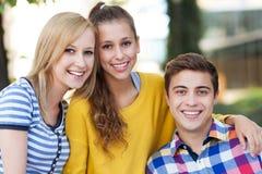 三青年人微笑 库存图片