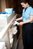Γυναίκα υπάλληλος πίσω-γραφείων που διπλώνει τα φύλλα Στοκ Εικόνα