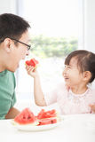 有吃果子的父亲的小女孩 免版税库存图片