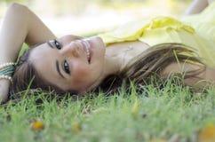 休息在公园的美丽的妇女 免版税库存图片