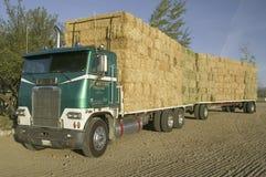 停放的卡车用整洁地被堆积的干草捆装载了 免版税库存照片