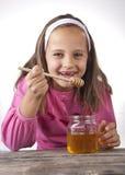 Το πορτρέτο του αστείου καλού μικρού κοριτσιού τρώει το μέλι Στοκ εικόνες με δικαίωμα ελεύθερης χρήσης