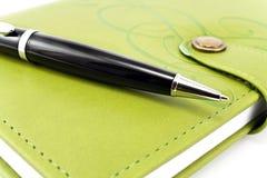 笔和绿色笔记本 免版税库存图片
