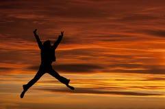 跳充满喜悦的女孩在日落 免版税库存照片