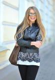 有微笑的袋子的时装模特儿佩带的太阳镜户外 免版税库存图片
