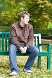 Νεαρός άνδρας στη συνεδρίαση πάρκων φθινοπώρου στον πάγκο Στοκ εικόνες με δικαίωμα ελεύθερης χρήσης